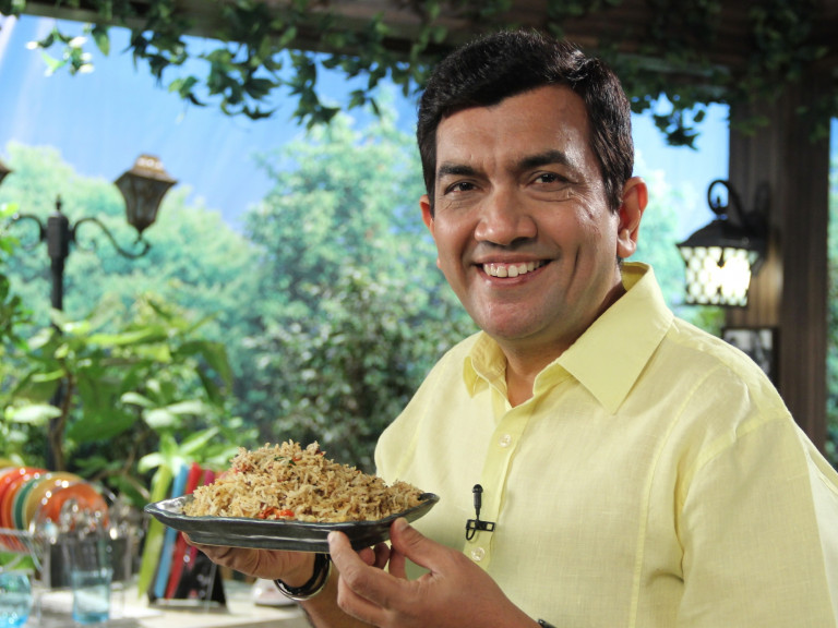 Television chef Sanjeev Kapoor holding a plate of rice.