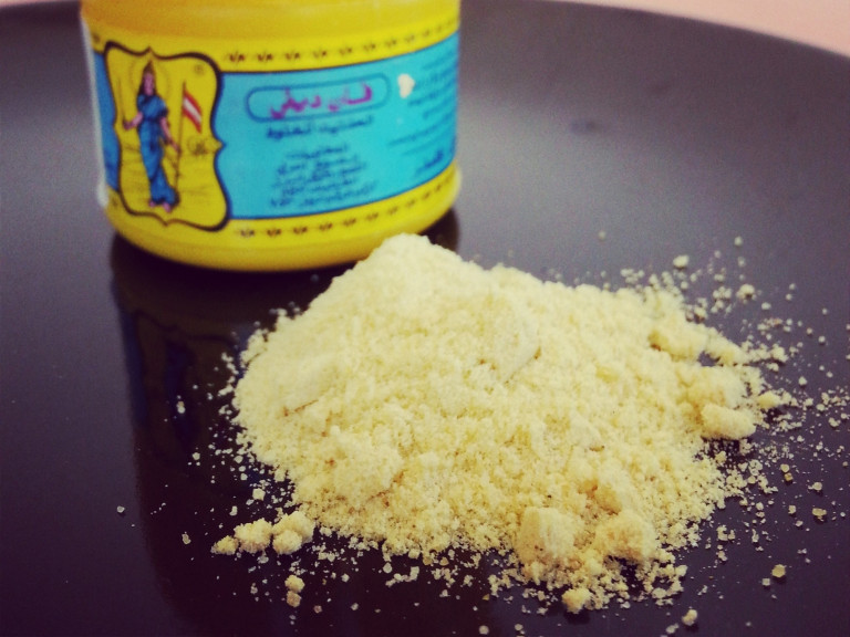A small pile of asafoetida powder with container in background.