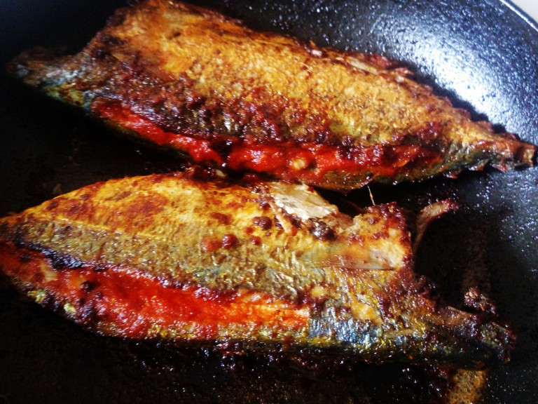 Two pieces of mackerel, stuffed with recheado paste, in frypan