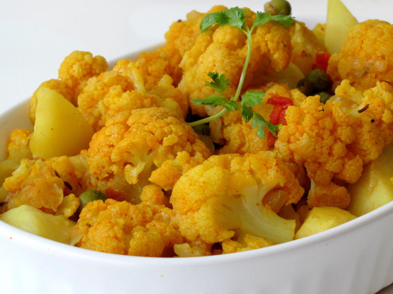 a serving dish, filled with the dry potato and cauliflower curry
