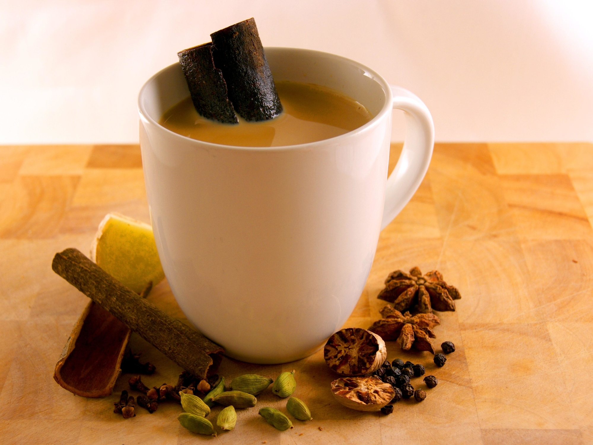 a cup of masala chai, surrounded by spices
