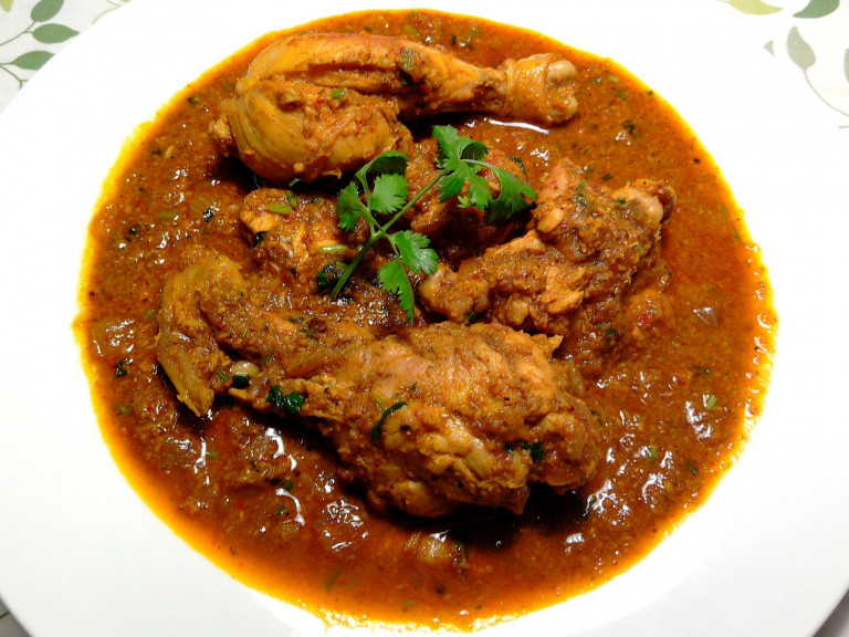 a serving bowl of chicken xacuti