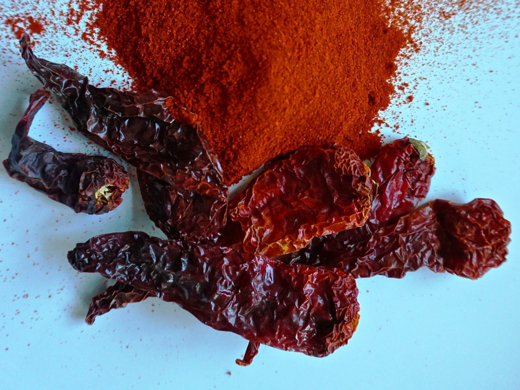 A pile of dried kashmiri chillies with some powdered chilli in background