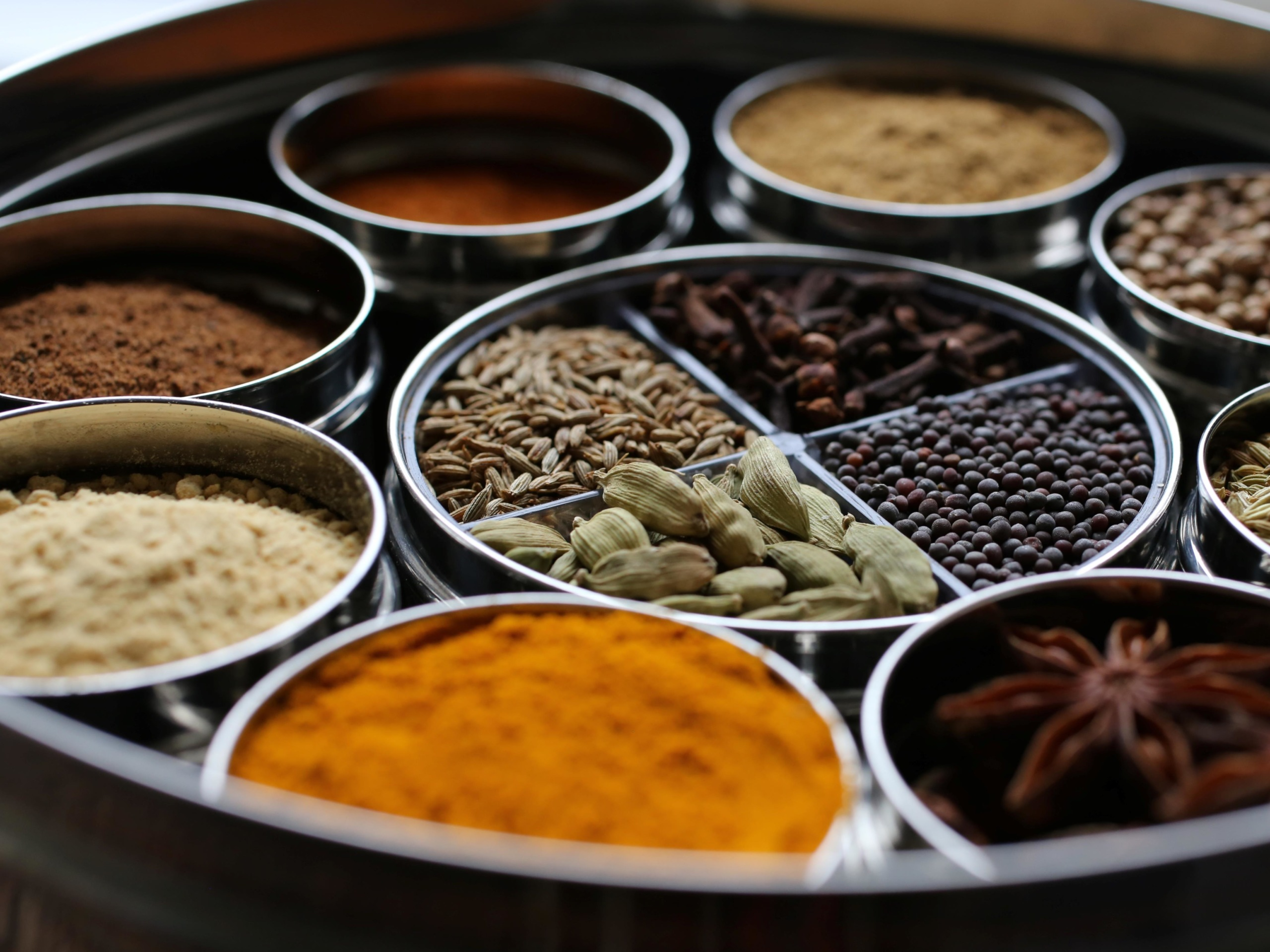 a spice tin filled with ground and whole spices