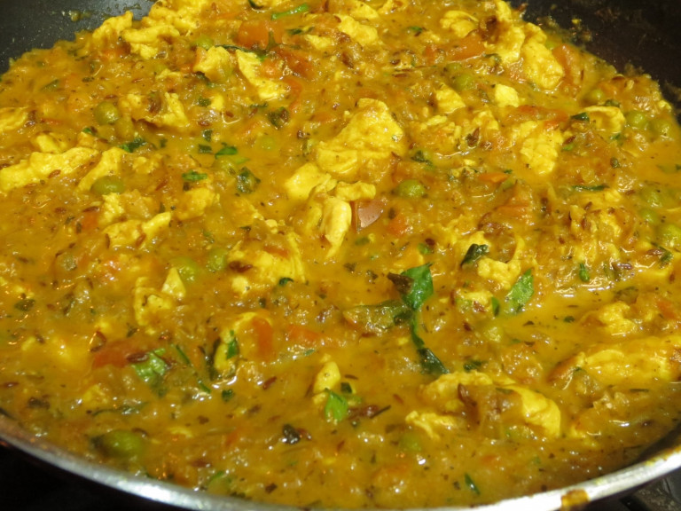 a serving bowl of dal with an omelette chopped into it