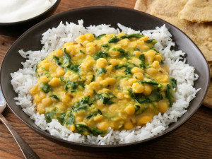 a plate of white rice with a serving of dal with spinach on top