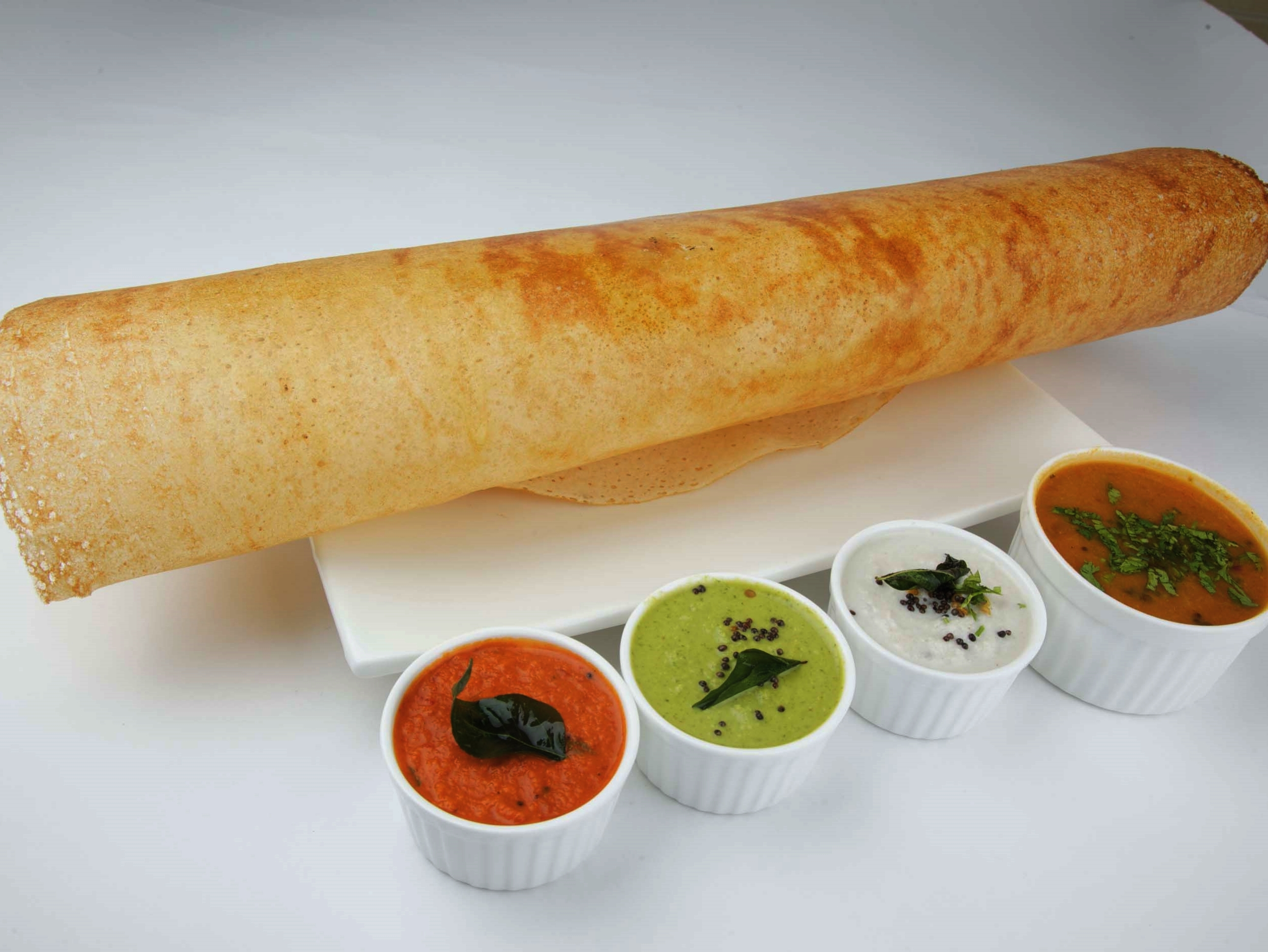 a dosa on a plate with sambar and chutneys in serving bowls