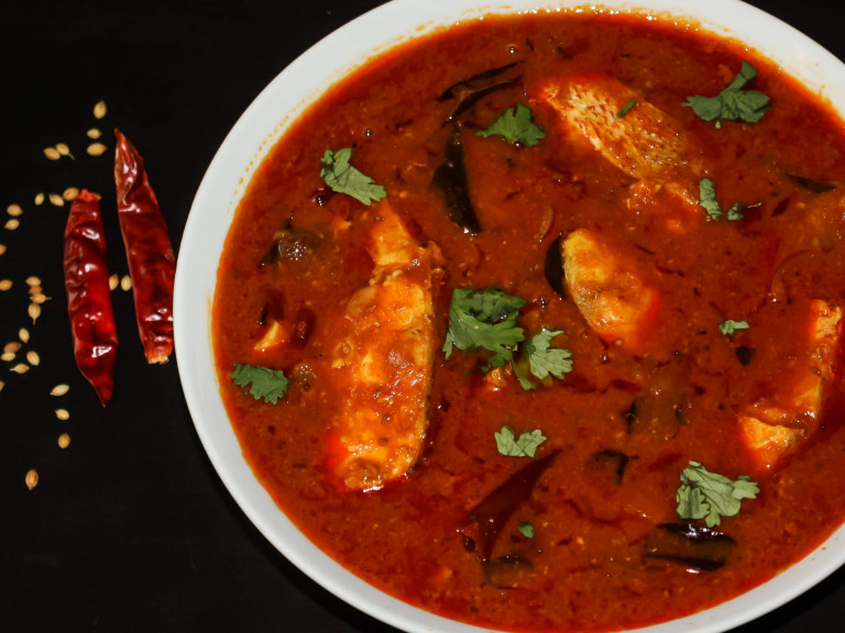A serving bowl of chennai fish curry, with some dried red chillies on the side.