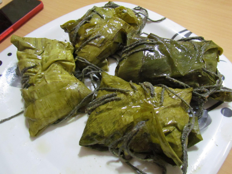 a platter of fish steamed with coconut and coriander in banana leaf parcels