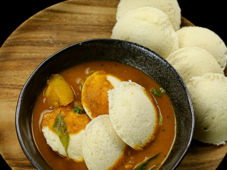 a bowl of sambar on a serving platter with idli