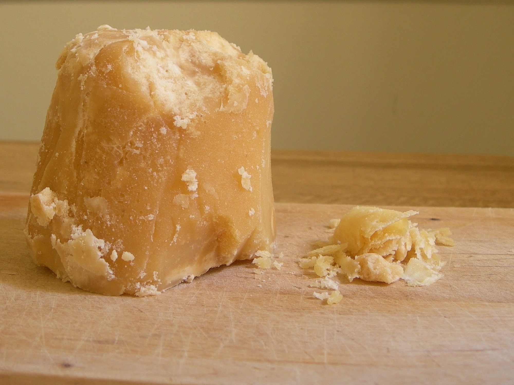 a blocki of jaggery, with some shaved pieces at the side