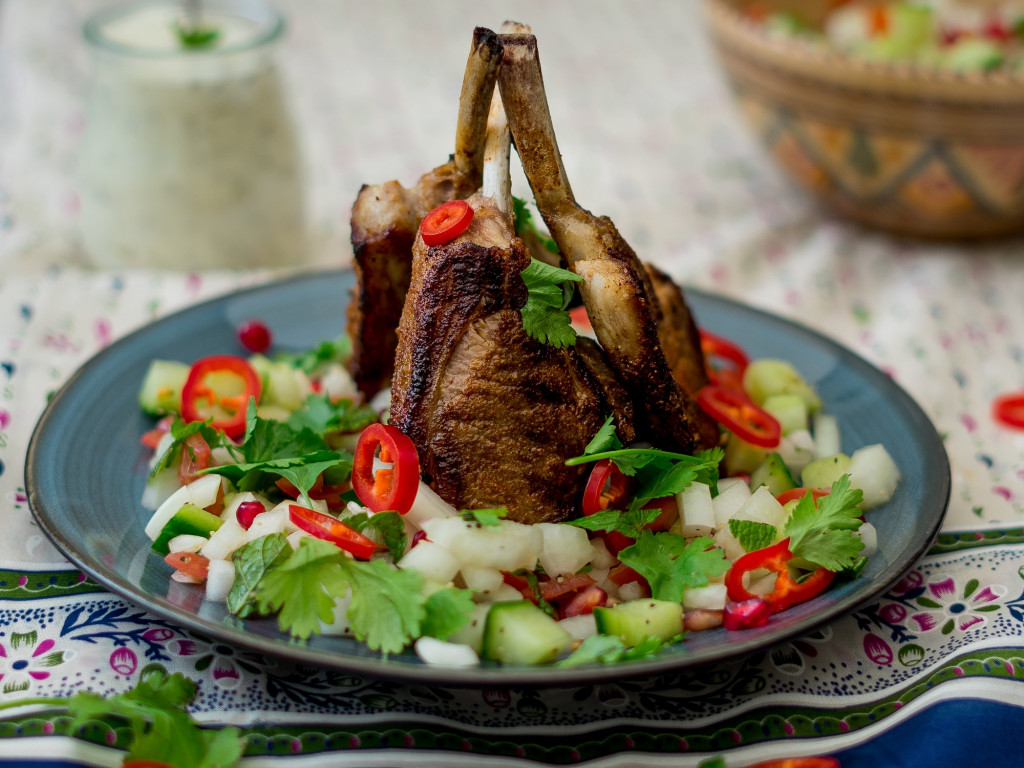 three barbecued lamb cutlets on a bed of kachumber
