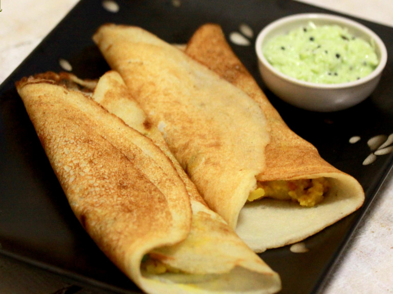 two masala dosa on a plate with serving dish of coconut chutney