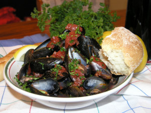 a bowl of mussels, cooked in recheado masala, with a portuguese dinner roll