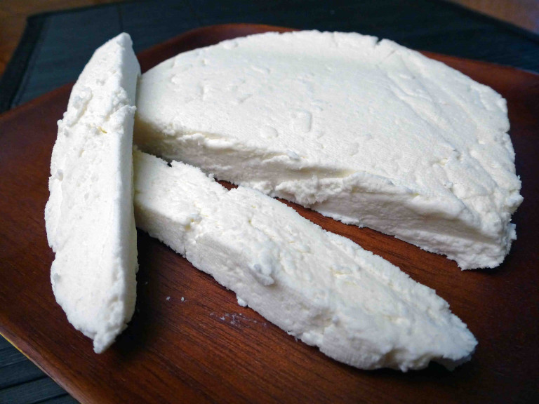a block of paneer, partly cut, on chopping board