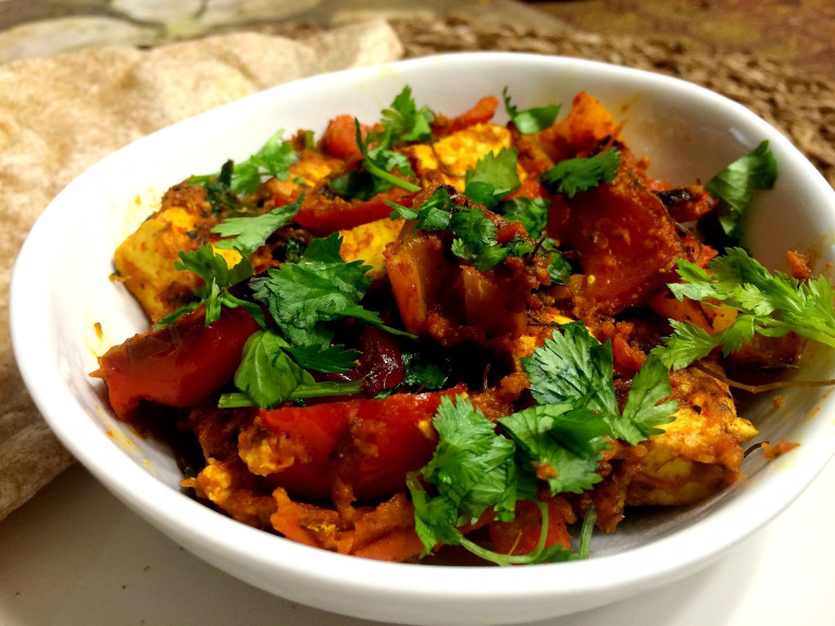 A serving bowl of paneer, capsicum and tomato