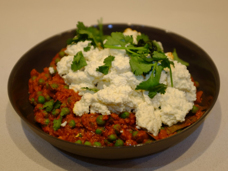 A serving bowl of paneer and peas