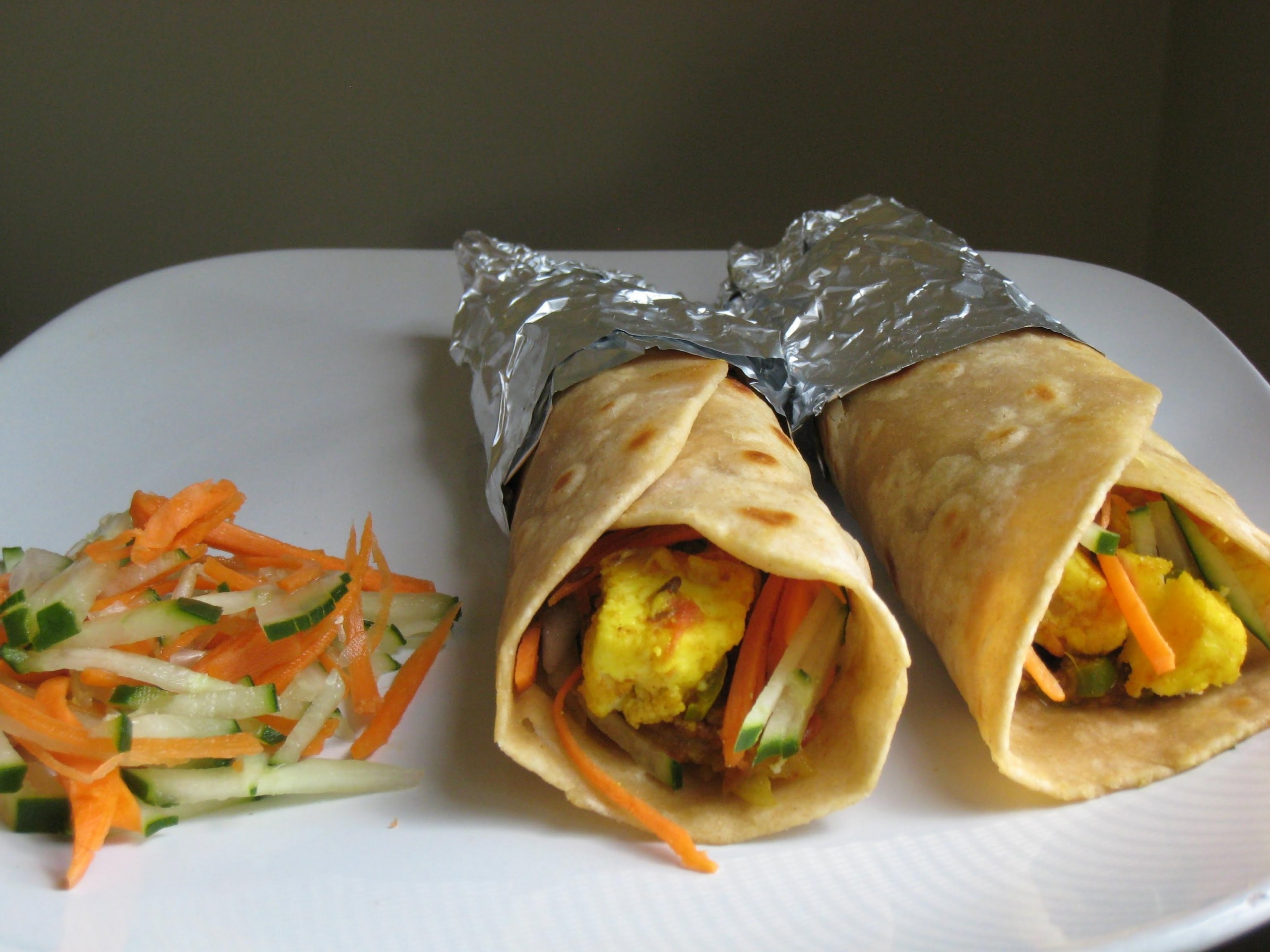 two paneer roti rolls on a plate with a serve of kachumber
