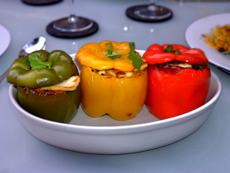 three differently coloured capsicums stuffed with paneer