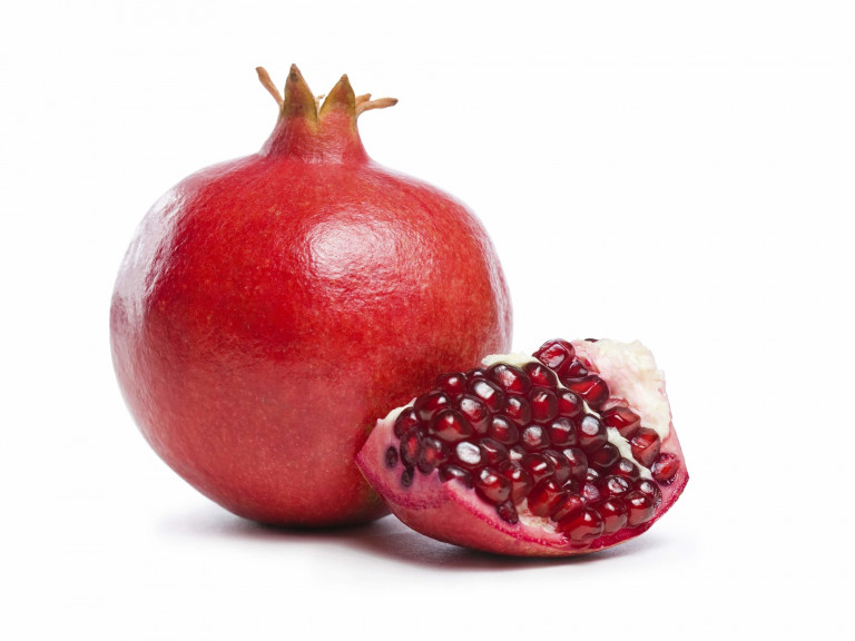 a whole pomegranate with a cut wedge in foreground
