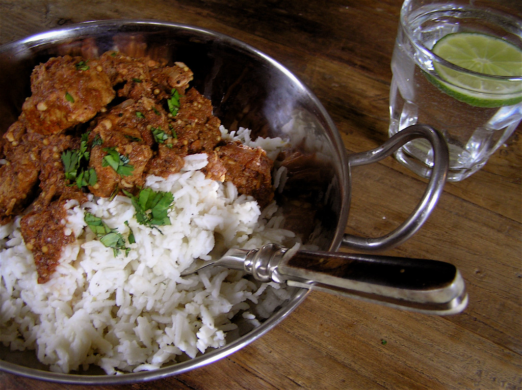 a serving of pork vindalu with rice and a glass of lime water