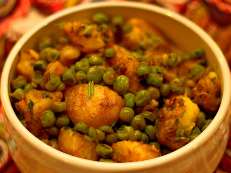 a serving bowl of dry potato and pea
