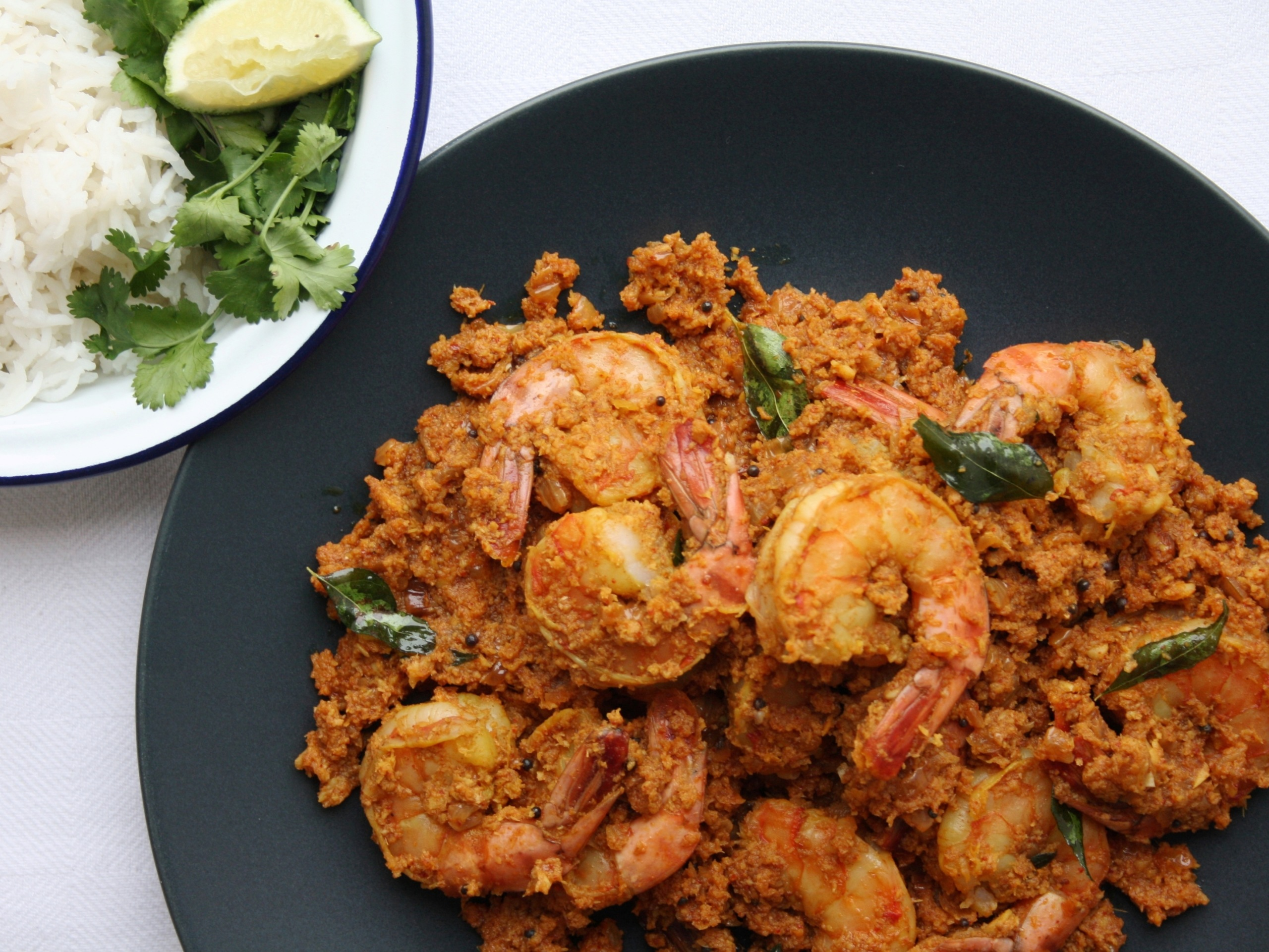 a plate of bengali prawns with a side dish of rice