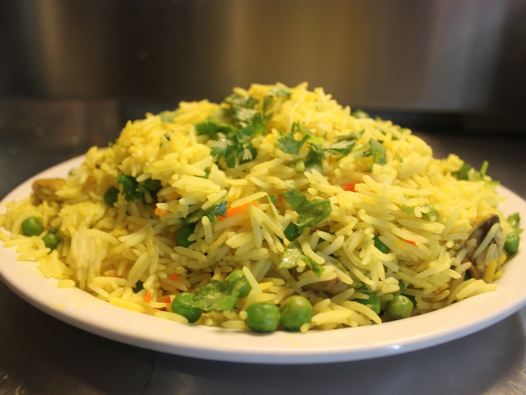 a serving bowl of pulao with peas