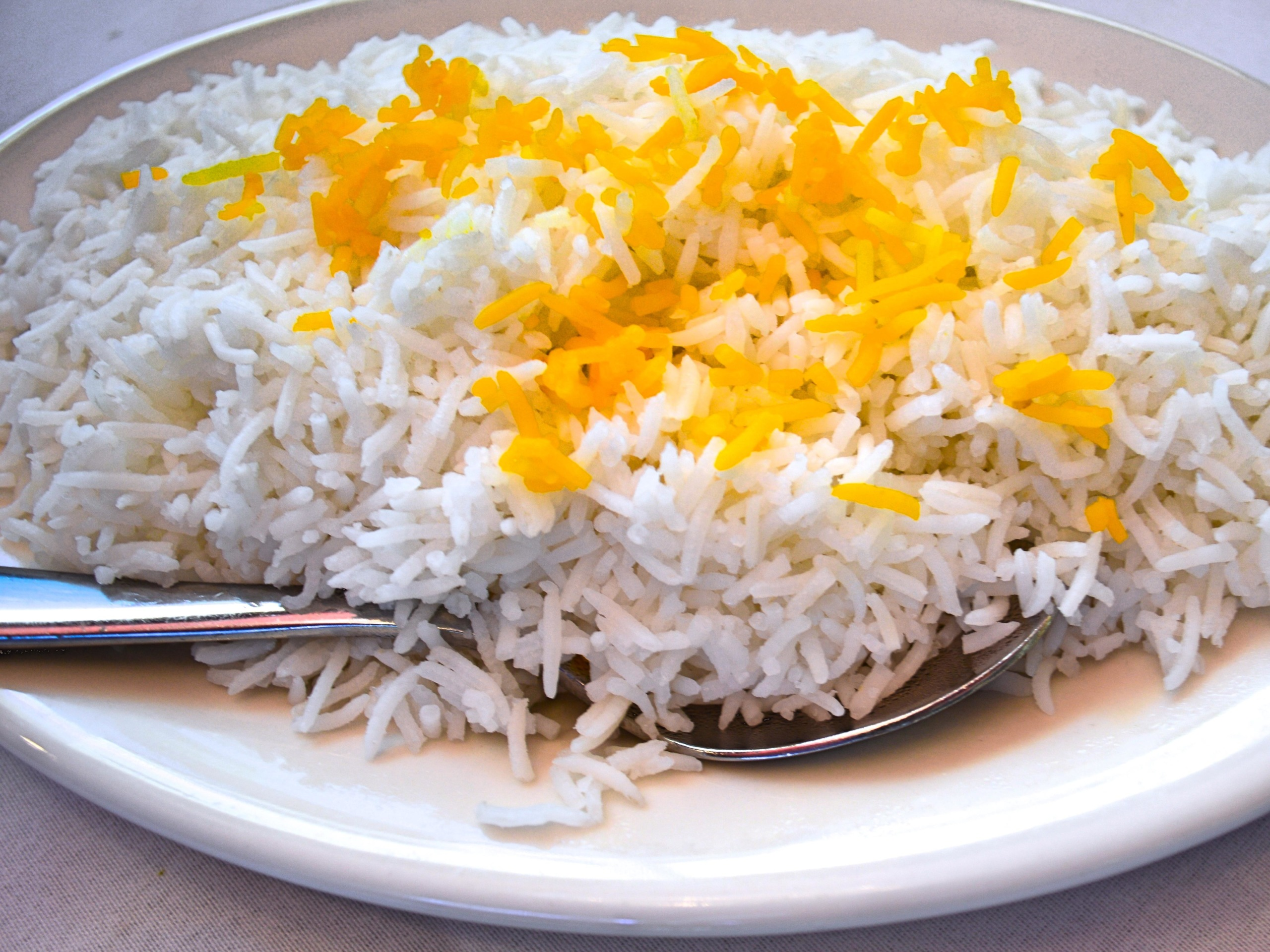 a bowl of cooked basmati rice, with some yellow rice decoration