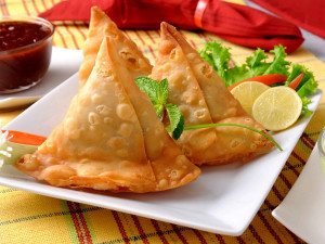 three samosas on a serving plate