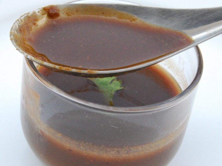 a jar of tamarind water with a spoon