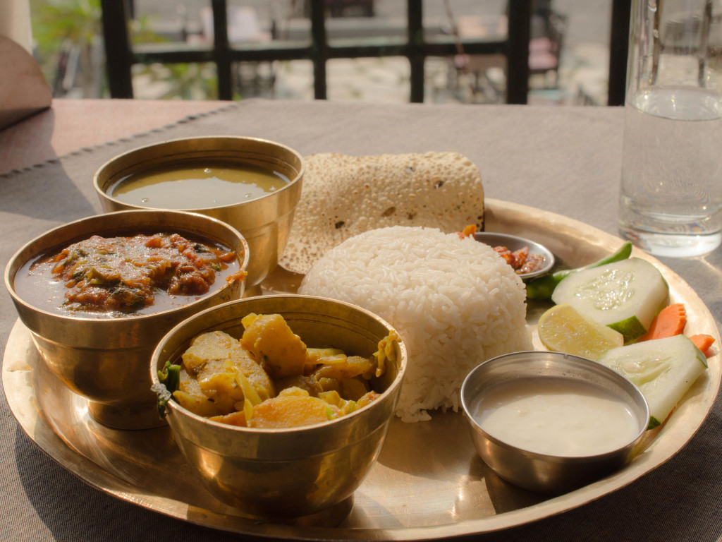 a simple vegetarian thali - bowls of rice, dal, vegetable curry and accompaniments on a serving platter