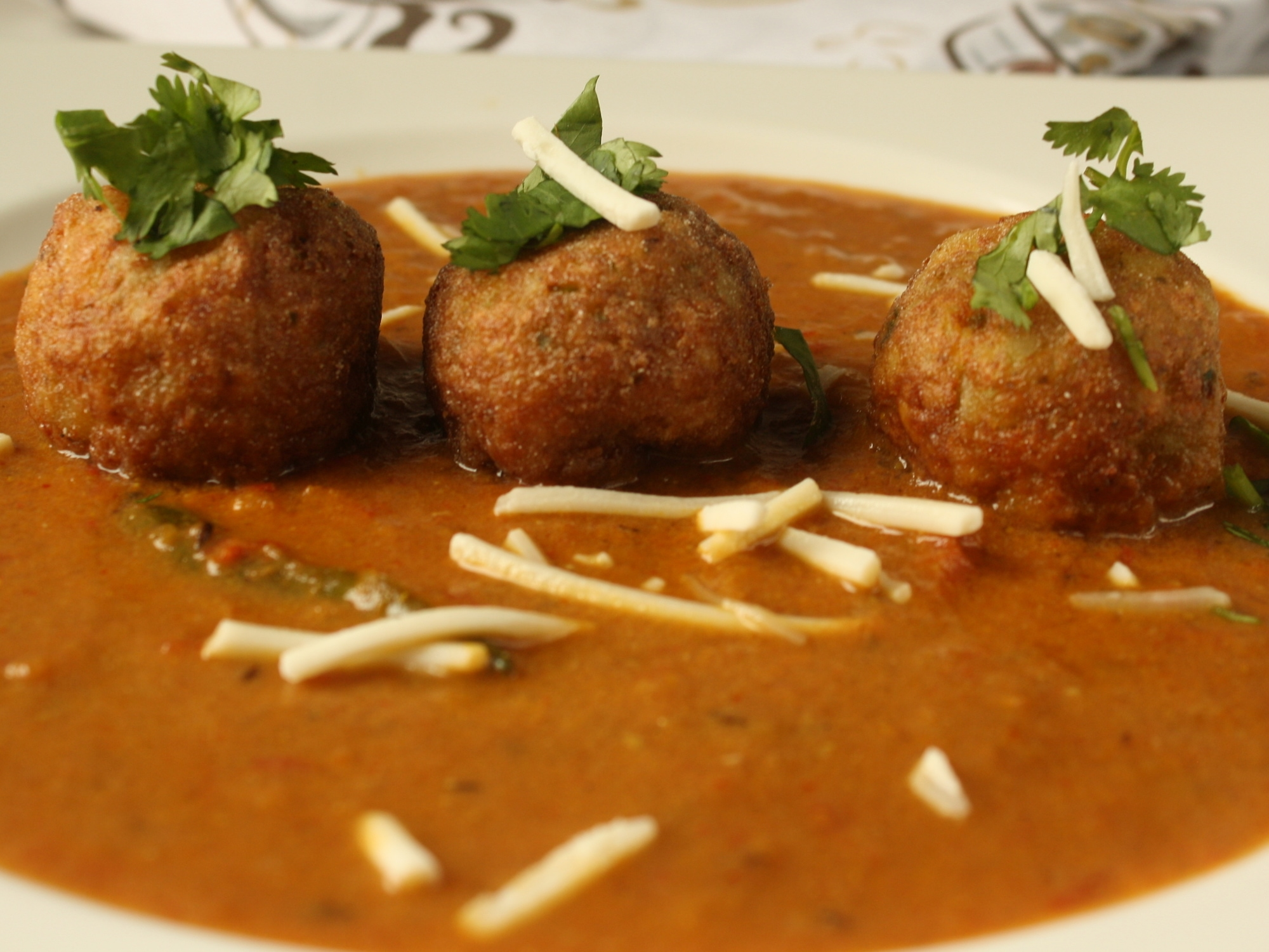 a serving dish of vegetable kofta curry